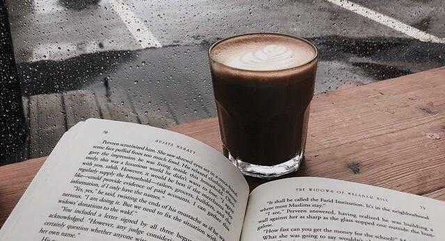 Copo com café na frente de um livro aberto, ambos em cima de uma mesa que está de frente para uma janela que mostra a rua chovendo.